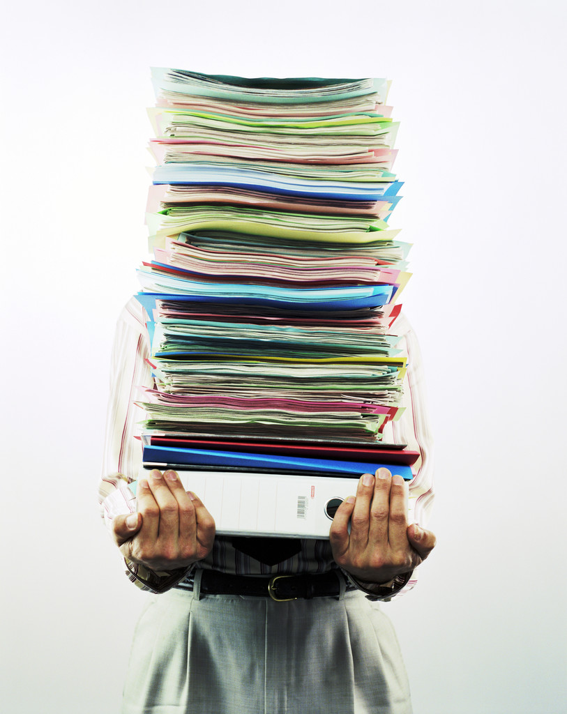 Businessman Carrying Pile of Files